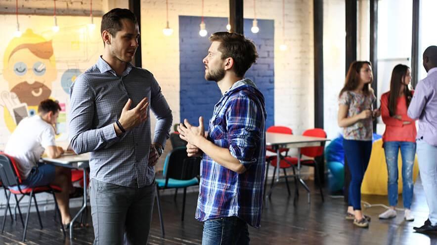 Deux étudiants discutants dans un espace de co-working